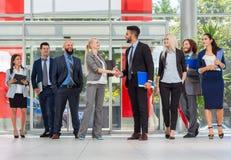 商人小组上司手震动在现代办公室,买卖人队握手报名参加合同 库存照片
