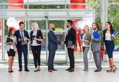 商人小组上司手震动欢迎姿态在现代办公室,买卖人队握手签合同 免版税库存照片