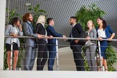 商人小组上司手震动欢迎姿态在现代办公室,买卖人队握手 免版税库存图片