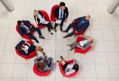 商人小组坐在圈子油罐顶部角钢视图,买卖人见面的椅子 库存图片