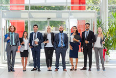 商人小组愉快的微笑常设线在现代办公室,买卖人行 免版税图库摄影