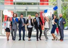 商人小组成功的激动的队在现代办公室,买卖人愉快的微笑 库存图片