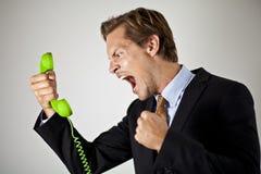 商人尖叫对电话 免版税库存图片