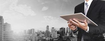 商人工作在数字式片剂的室外和城市全景背景 免版税图库摄影