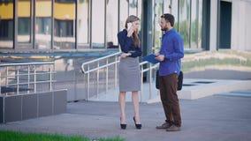 商人工作得外面 站立近的办公室的女性销售主任说在电话里 人打扮  影视素材