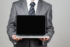 商人常设姿势手举行笔记本膝上型计算机 库存图片