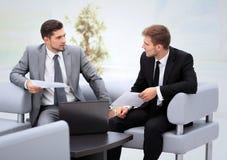 商人开会议在表附近在现代办公室 免版税库存图片