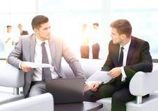 商人开会议在表附近在现代办公室 图库摄影