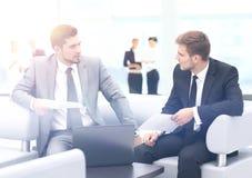商人开会议在表附近在现代办公室 免版税图库摄影