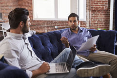 商人开关于沙发的非正式会议在现代办公室 库存照片