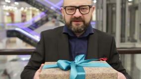 商人微笑礼物礼物盒在手中 关闭 股票录像