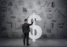 商人感人的大具体美元的符号后面看法在backgound的与事务乱画 免版税库存照片