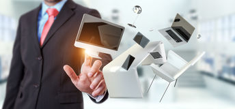 商人感人的飞行书桌膝上型计算机电话和片剂与喂 免版税库存照片