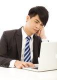 年轻商人感受疲倦了或恼怒与膝上型计算机 免版税库存照片