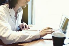 年轻商人或学生,长的头发,在键盘的运作的文字在与开放膝上型计算机的窗口附近 图库摄影