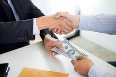 商人或政客收取贿款和与在衣服的金钱握手,腐败商业交换概念 免版税图库摄影