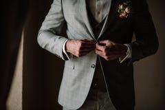 商人或新郎白色衬衣的有有薄荷味的领带的紧固他的蓝色斜纹软呢夹克按钮  免版税库存照片
