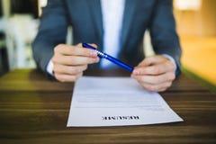 商人或求职者回顾他的在他的书桌上的履历在找到与笔的新的工作的送前 免版税图库摄影