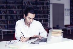 商人或集中工作的大学生在膝上型计算机,写在一个笔记本在图书馆里 库存照片