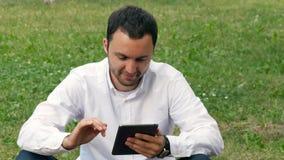 商人户外与数字式片剂个人计算机一起使用在公园 放松与室外数字式的片剂 库存照片
