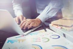 商人手运转的膝上型计算机两次曝光在木书桌上的在早晨光的办公室 现代工作的概念 免版税图库摄影
