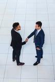 商人手震动欢迎姿态油罐顶部角钢视图,两个商人做成交握手报名参加 库存图片