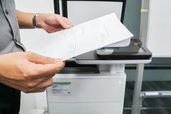 商人扫描的举行纸在办公用打印机 免版税库存照片