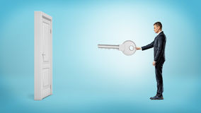 商人把握一个巨型银色关键准备打开在蓝色背景的白色被隔绝的门 免版税库存照片