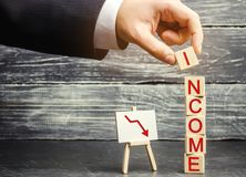 商人投入与词收入和下来箭头的一个立方体 减少赢利和收入的概念 降低薪金,工资率 免版税库存照片