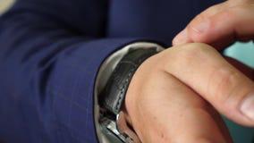 商人投入他的手表并且调直他的夹克袖子 人的样式无尾礼服 概念的时兴 股票视频
