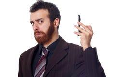 商人投入他的远离他的耳朵的电话 免版税库存图片
