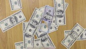 商人投掷在木桌,金钱背景上的美元  股票录像