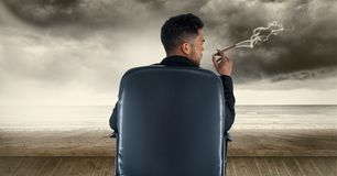 商人抽烟的雪茄背面图,当坐椅子时 图库摄影
