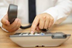 商人拨与耳机的一个电话号码在他的手上 免版税库存图片