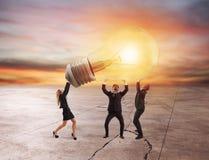 商人拿着一个电灯泡 新的想法和公司起动的概念 免版税库存照片