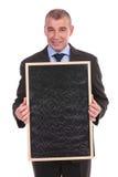 商人拿着一个空白的黑板 免版税库存图片