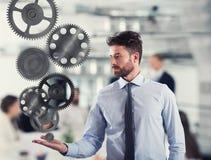 商人拿着一个齿轮系统 企业机制的概念 免版税图库摄影