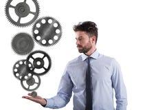 商人拿着一个齿轮系统 企业机制的概念 免版税库存照片
