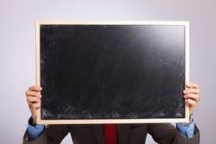 年轻商人拿着在他的面孔前面的黑板 库存图片