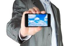 商人拿着有云彩计算的概念的巧妙的电话 免版税图库摄影