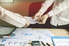 商人拿着有队的银行,并且在我的书桌上的纸点燃日落背景 免版税库存图片