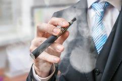 商人拿着蒸发器和抽电子香烟 免版税库存图片