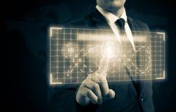 商人按在高科技显示的一个按钮 库存图片