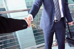 商人握手在机场-商务旅游概念 免版税库存照片