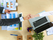 商人握手,坐在桌上 免版税库存图片