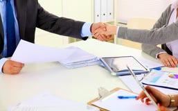 商人握手,坐在桌上 免版税图库摄影
