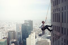 商人攀登与绳索的一个大厦 决心的概念 免版税库存图片