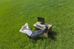 商人放松的认为在绿色领域的书桌 免版税库存照片