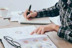 商人文字某事在笔记本纸和企业财务在桌上弄脏的报告文件,会计 免版税图库摄影