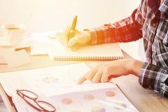 商人文字的手某事在笔记本纸和企业财务在桌上弄脏的报告文件 免版税库存照片